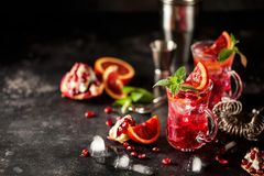 Red cocktail with blood orange and pomegranate. Refreshing summer drink on dark background royalty free stock images