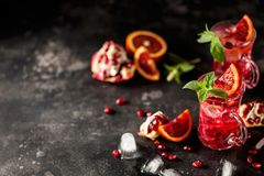 Red cocktail with blood orange and pomegranate. Refreshing summer drink on dark background stock image