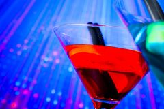 Red cocktail with blue light disco background with space for text Stock Image