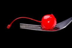 Red cocktail cherry on a fork Stock Photo
