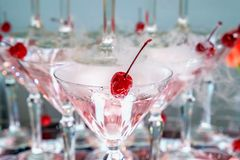 Red cocktail cherry in a glass. With a pink alcoholic drink. Closeup view Royalty Free Stock Photos