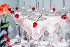 Red cocktail cherry in a glass. With a pink alcoholic drink. Closeup view Royalty Free Stock Image