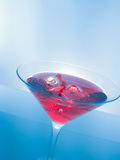 Red cocktail drink with ice cubes on blue light tint background, fun and dance disco Royalty Free Stock Photos