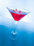 Red cocktail drink with ice cubes on blue light tint background, fun and dance disco Stock Images