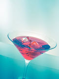 Red cocktail drink with ice cubes on green light tint background, fun and dance disco Royalty Free Stock Photos