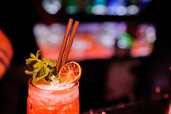 red cocktail in glass with straws and mint in night club Stock Photo