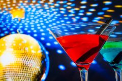 Red cocktail with golden sparkling disco ball background with space for text Royalty Free Stock Images