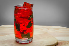 Red cocktail with ice. Redt cocktail with ice and mint on a wooden table Royalty Free Stock Photos