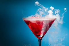 Red cocktail with ice vapor. Blue background Stock Photography