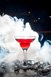 Red cocktail with ice vapor, blue background Royalty Free Stock Photography