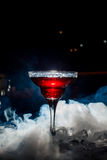 Red cocktail with ice vapor, blue background Royalty Free Stock Image