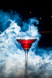 Red cocktail with ice vapor, blue background Royalty Free Stock Photos