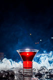 Red cocktail with ice vapor, blue background Stock Photo