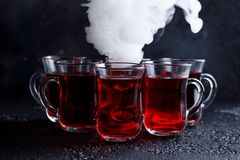 Red cocktail with ice vapor. red cold tea with steam on a black background. Royalty Free Stock Photo