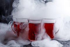 Red cocktail with ice vapor. red cold tea with steam on a black background. Stock Photo