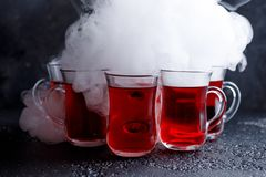 Red cocktail with ice vapor. red cold tea with steam on a black background. Royalty Free Stock Photography