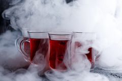 Red cocktail with ice vapor. red cold tea with steam on a black background. Stock Images