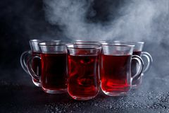 Red cocktail with ice vapor. red cold tea with steam on a black background. Royalty Free Stock Photos