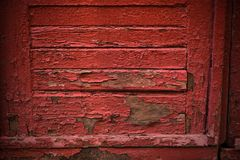 Red wooden door with cracked paint. Fragment of an old red wooden door with cracked paint royalty free stock image