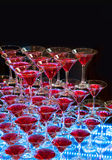 Red cocktail in Martini glasses. On a black background with blue neon lighting Stock Photos