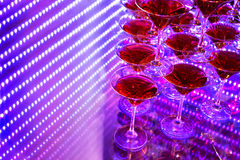 Red cocktail in Martini glasses. Decorated on a background with purple neon lighting, copy space Royalty Free Stock Images