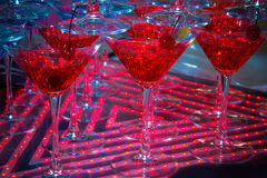 Red cocktail in Martini glasses. Decorated with cherries on a background with red neon lighting Stock Photo