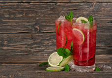 Red cocktail with mint, lime and ice Stock Photos