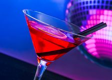 Red cocktail with sparkling disco ball background with space for text Royalty Free Stock Photography