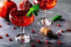 Red cocktail with sparkling wine and pomegranate seeds. On rustic background royalty free stock photos