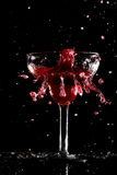 Red cocktail splashes on black background Royalty Free Stock Photos