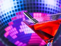 Red cocktail and straw with sparkling disco ball background with space for text Royalty Free Stock Photo