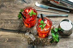 Red cocktail with strawberry, mint leaves, ice. Drink bar Stock Images
