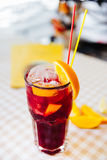 Red cocktail with straws and orange wedge in high glass Royalty Free Stock Photography