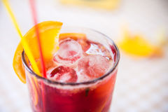 Red cocktail with straws and orange wedge in high glass Stock Images