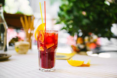 Red cocktail with straws and orange wedge in high glass Stock Photos