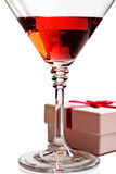 Red cocktail with umbrella. Red cocktail in martini glass with umbrella and gift box royalty free stock photography