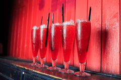Red cocktails in high glasses. On wall Stock Photography
