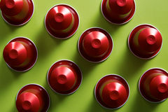 Red coffee capsules on green background Royalty Free Stock Photos