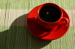 Red Coffee Cup. And saucer filled with coffee sitting on a place mat. Sunlight comes in from upper right corner producing a shadow to the left Royalty Free Stock Images