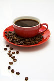 Red coffee cup and beans. Coffee cup on the beans. Close up Stock Photo