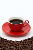 Red coffee cup and beans. Coffee cup on the beans. Close up Royalty Free Stock Photography