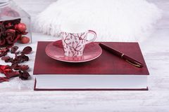 Red coffee cup, book and pen on white wooden background.  Royalty Free Stock Photos