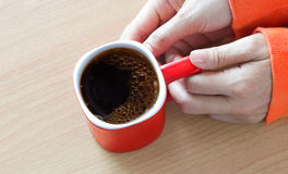 Red coffee cup with bubble in woman hand on wooden table Royalty Free Stock Photos