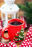 Red coffee cup with candle and spruce on the background Royalty Free Stock Photography