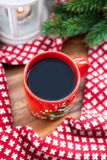 Red coffee cup with candle and spruce on the background Stock Images