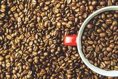 Red coffee cup in coffee beans overhead. Freshly roasted coffee beans and cup Royalty Free Stock Photos