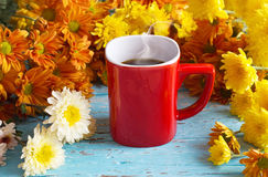 Red coffee cup and colorful flowers on vibrant wooden background Stock Images