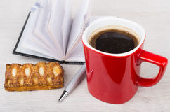Red coffee cup, cookie, opened notepad and pen Stock Photo