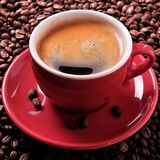 Red coffee cup espresso roasted beans close up square format Royalty Free Stock Image