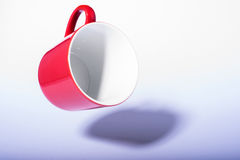 Red coffee cup flying over white background with shadow Stock Photos